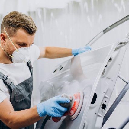 Car mechanic polishing car before painting